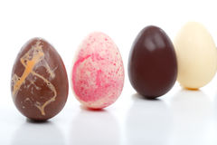 Four Decadent Easter Eggs. Four unique hand made easter eggs standing in a row.  Flavours are: Chocolate with orange chips, white chocolate and pieces of Royalty Free Stock Photo