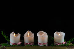 Four decorated advent candles at black background Stock Photos