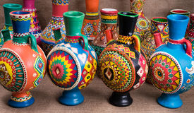 Four decorated colorful handcrafted pottery jugs on sackcloth ba Stock Photography
