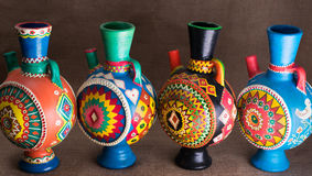Four decorated colorful handcrafted pottery jugs on sackcloth ba Stock Photo