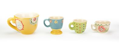 Four decorative ceramic teacups in a row. White background. Four pretty ceramic teacups in a row on white background. Varying colours, patterns and sizes in stock image