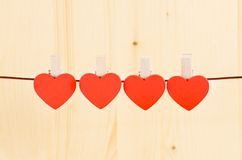 Four decorative red hearts hanging on wood background, concept of valentine day Royalty Free Stock Image