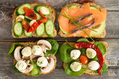 Four delicious open sandwiches on a picnic table. Four delicious open wholewheat sandwiches on a wooden picnic table topped with smoked salmon, avocado Royalty Free Stock Photos