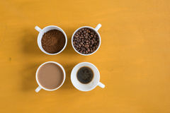 Four different cups on a yellow background Royalty Free Stock Photography