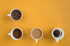 Four different cups on a yellow background Royalty Free Stock Images