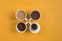 Four different cups on a yellow background Stock Photo