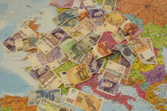 Four different currencies laid out on the map of Europe Stock Images