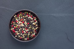 Four different kinds of peppercorns in clay bowl on stone background, copy space, top view stock photos
