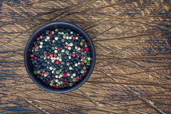 Four different kinds of peppercorns in clay bowl on wooden background, copy space, top view royalty free stock photo