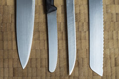 Four different knives in a row on a wooden background Stock Images