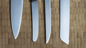 Four different knives in a row on a wooden background Royalty Free Stock Image