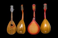 Four different mandolins isolated on black background. stock photos
