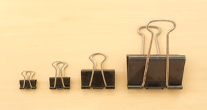 Four Different Size of Black Paper Clips. On a Wooden Surface Table Stock Photos