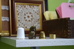 Four different thimbles on a wooden shelf on the background of knitted pictures and labels for clothes royalty free stock images