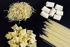 Different types of pasta are laid out on black background. Four different types of pasta are laid out on black background royalty free stock images