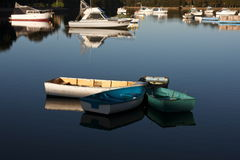 Four dinghys in a group on the water. Four dinghys tied together on a calm still morning lake Stock Image