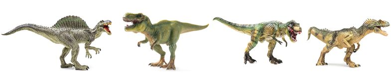 Four dinosaurs figurines in a row. On white background royalty free stock photo