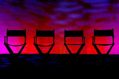 Four Director's Chairs silhouette on Swirl Stage. Silhouette of a four traditional wood and canvas Director's Chair on a red and purple stage background stock photography