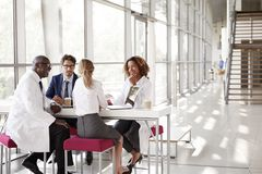 Four doctors talking at a table in a modern hospital lobby royalty free stock photography