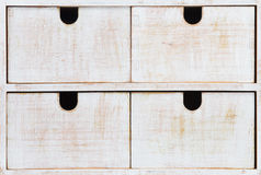 Four drawers. Four white wooden drawers with black holes Stock Image