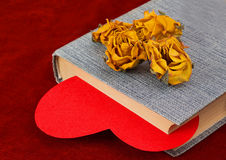 Four dried yellow roses lying on the book with red heart Stock Photo
