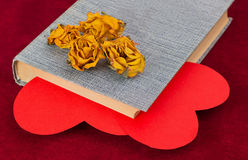 Four dried yellow roses lying on the book with two red hearts Stock Photos