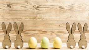 Four easter bunnies and three easter eggs. In front of a wood background Royalty Free Stock Photography