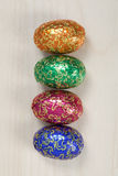 Four easter eggs. 4 bright coloured easter eggs in a row sitting on a wood surface Stock Photos