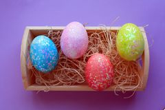 Colorful Easter eggs in nesting box on purple background. Four Easter eggs on blue pink yellow and red in a nesting box with nesting material above shot with a stock photo