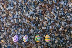 Four easter eggs lie on the pebbles. Four easter eggs lie on the grey pebbles outdoor Royalty Free Stock Photo