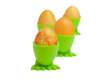 Golden eggs in cups Stock Photos