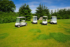 Four eco transporters on golf course Stock Photo