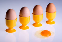 Four egges and an accident. Four egges in egg cups and another one, alone, opened Royalty Free Stock Photos