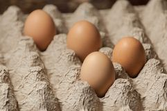 Four Eggs in a Cardboard Egg Tray. Four large eggs in a textured cardboard egg tray shot horizontally with selective focus Royalty Free Stock Images