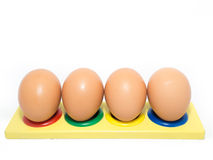 Four Eggs on Coloured Holes. On a white isolated background Stock Photos