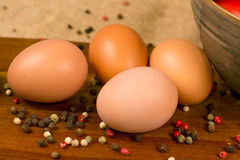 Four eggs with decorative pepper on a wooden surface and canvas Stock Images