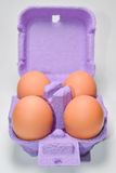 Four eggs in purple packaging Stock Photo
