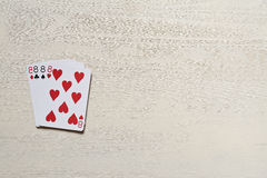 Four eight playing cards on light desk. Risk and luck casino game poker abstract with copyspace Royalty Free Stock Images