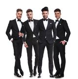 Four elegant young men in tuxedos standing together. On white background, looking relaxed. full body picture stock photos