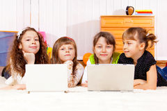 Four elementary aged girls. Lying in front of laptops Royalty Free Stock Image