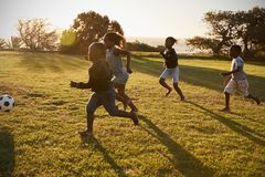 Four elementary school kids playing football in a field royalty free stock images