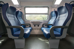 Four empty blue seats facing each other in modern European train Royalty Free Stock Images