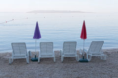 Four empty deck chair and parasol Royalty Free Stock Image