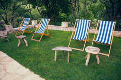 Four empty deck chairs with white and blue stripes Stock Photography