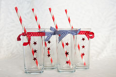 Four empty festive glasses with straws Stock Image