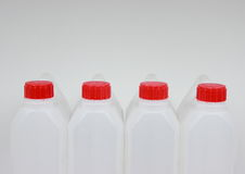 Four empty jerrycans of white plastic with red lids Royalty Free Stock Image