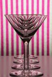 Four empty glasses for martini and vermouth standing in line with white and pink striped background. Four empty transparent glasses for martini and vermouth royalty free stock photos