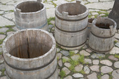 Four empty water barrels on stony yard Royalty Free Stock Photography