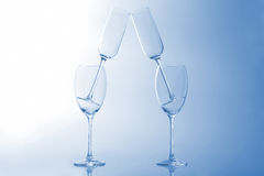 Four empty wine glass on a light blue background Stock Photos