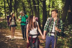 Four excited friends tourists are walking in autumn forest, talking and enjoying, wearing comfortable outfits for hiking,  holding. Hands, two lovely couples Royalty Free Stock Photo